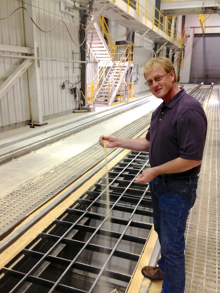 Max Schwader, a farmer from Winfred, demonstrates how soybean meal falls onto the conveyor belt from rail cars for storage in silos or direct loading onto ships. @ the AGP facility